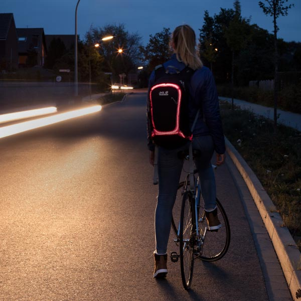 Woman carrying backpack at night